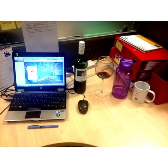 Agency essentials: laptop, bottle of wine, coffee, water.